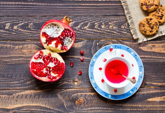 Thé aux fruits avec citron, lait, miel, orange, grenade, sur une table en bois