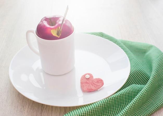 Thé aux fruits dans une tasse blanche avec un couvercle de pomme.