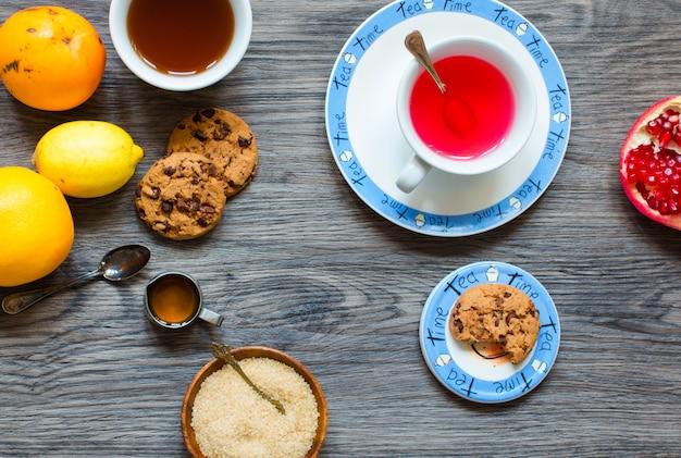 Thé aux fruits avec de la grenade au lait et au miel citronné sur un fond en bois
