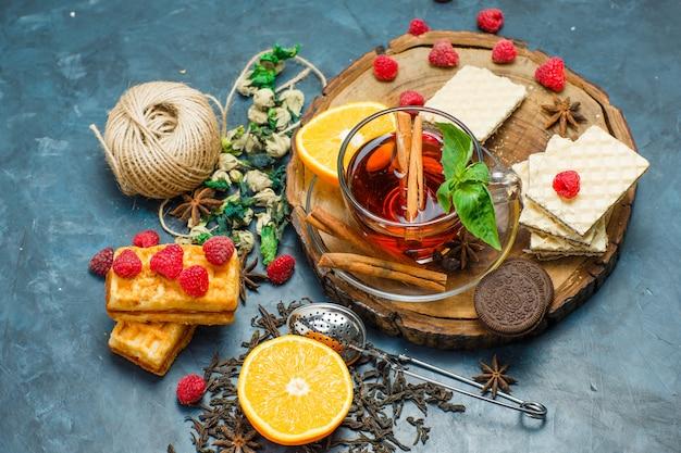 Thé aux herbes, fruits, épices, biscuits, passoire, fil dans une tasse sur planche de bois et fond de stuc, pose à plat.