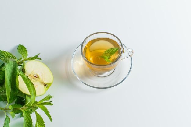 Thé aux herbes, pomme dans une tasse sur fond blanc, pose à plat.