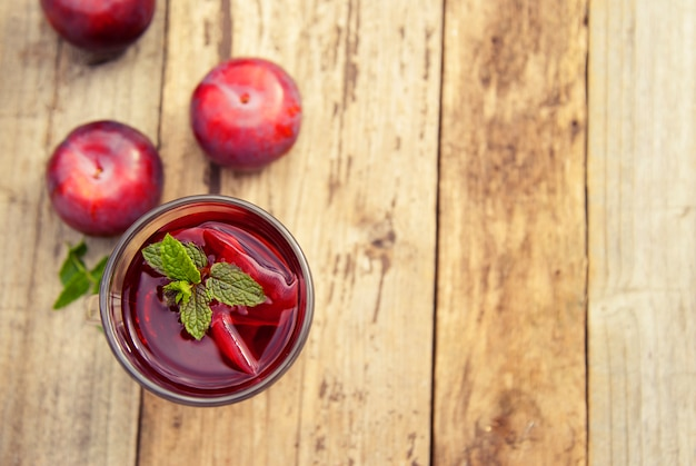 Thé aux herbes rouges dans une coupe en verre avec des prunes sur une table en bois.