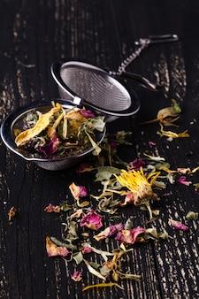 Thé aux herbes sec posé sur une table en bois