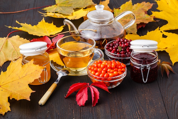 Thé de baies d'argousier avec du miel sur une table en bois en automne enveronment