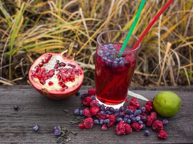Thé de baies et de fruits en verre sur une table en bois. récolte, thé chaud d'automne automne hiver chaud, boisson immunitaire.