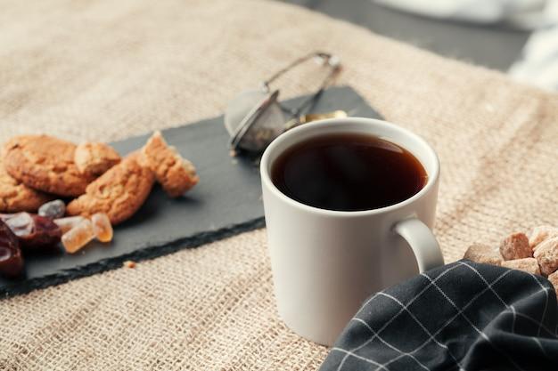 Thé avec des biscuits sur fond d'un sac