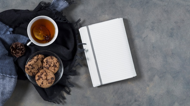 Thé avec des biscuits sur le plaid près de cahier