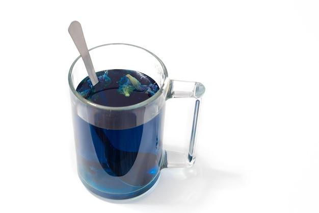 Thé bleu thaïlandais dans une tasse en verre et cuillère sur fond blanc isolé