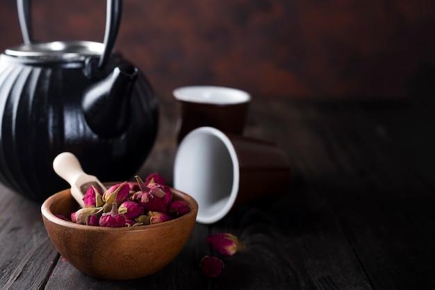 Thé de boutons de rose sur un bol en bois avec théière
