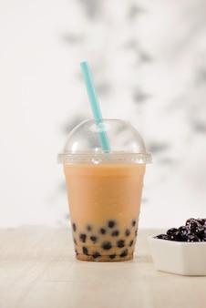 Thé à bulles de lait fait maison dans des gobelets en plastique sur table.