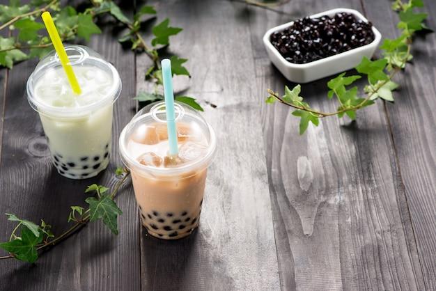 Thé à bulles laiteux avec perles de tapioca dans une tasse en plastique