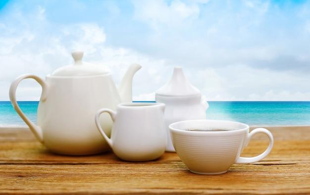 Thé café situé sur la table en bois sur le fond de la plage de l'été. sable et mer et ciel