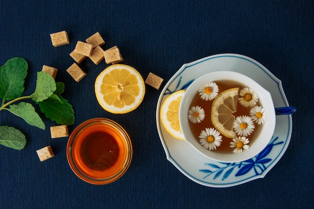 Thé à la camomille au citron, bol de miel, morceaux de sucre dispersés dans une tasse et sauce sur fond de napperon sombre, à plat.