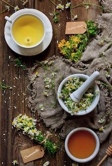 Thé à la camomille au miel naturel, camomille dans un mortier et bouquets de millepertuis