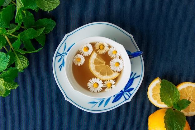 Thé à la camomille en bonne santé avec des citrons et des feuilles dans une tasse et de la sauce sur fond de napperon sombre, gros plan.
