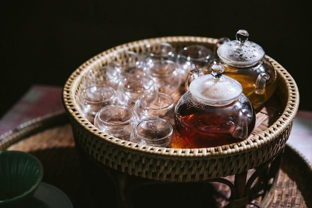 Thé de camomille chaud dans une théière en verre avec des verres vides dans un panier pour les testeurs.