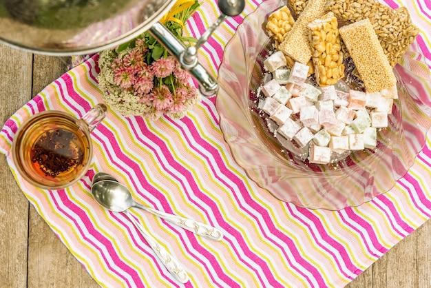 Thé à la camomille et divers bonbons sur une assiette.