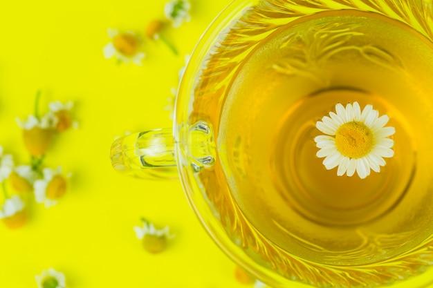 Thé à la camomille avec une fleur dans une tasse de près