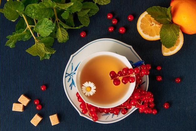 Thé à la camomille avec groseilles rouges, citrons, morceaux de sucre et feuilles dans une tasse et sauce sur fond de napperon sombre, à plat.