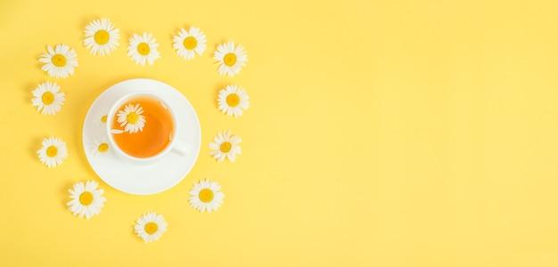 Thé à la camomille sur jaune avec espace de copie.
