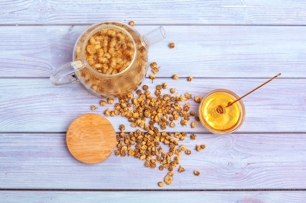 Thé à la camomille sain dans une tasse en verre. théière, petit pot de miel