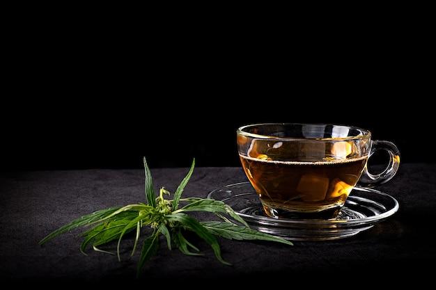 Thé de cannabis dans une tasse en verre clair avec une feuille et une tige vertes de marijuana