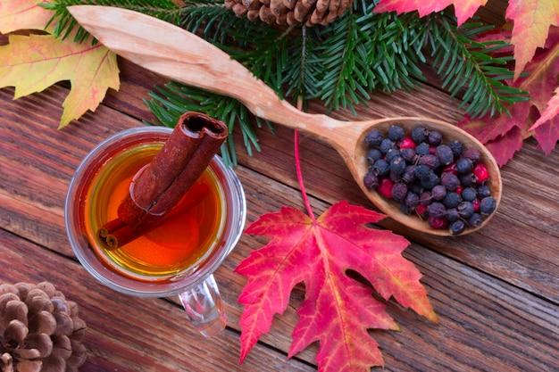 Thé à la cannelle et au citron, feuilles d'automne colorées d'érable, baies d'aubépine dans une cuillère en bois
