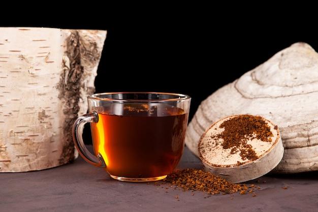 Thé chaga dans une tasse transparente sur fond sombre.