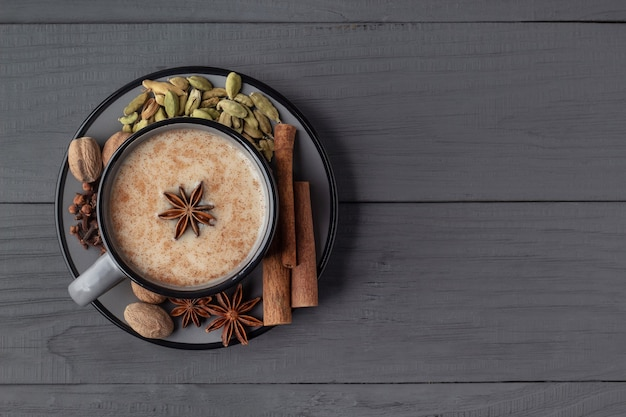 Thé chai masala indien traditionnel et condiments dans une tasse de fond en bois gris vue de dessus