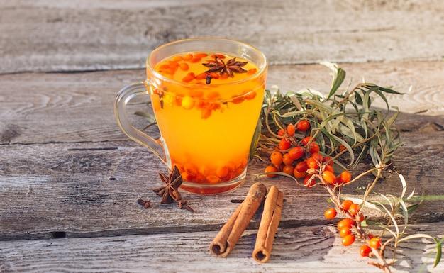 Le thé chaud à l'argousier aux vitamines dans une tasse se dresse sur une vieille relaxation en bois et à base de plantes médicinales