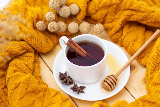 Thé chaud aromatique à la cannelle recouvert d'une écharpe chaude sur un fond d'automne en bois. louche de miel avec du miel