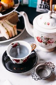 Thé chaud aux bleuets et aux pois, servi dans une tasse vintage en porcelaine avec infuseur à thé en acier inoxydable