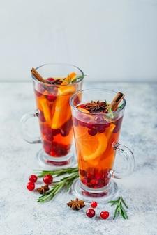 Thé chaud aux tranches d'orange, canneberges et romarin dans de grands verres. boissons chaudes pour l'hiver et noël