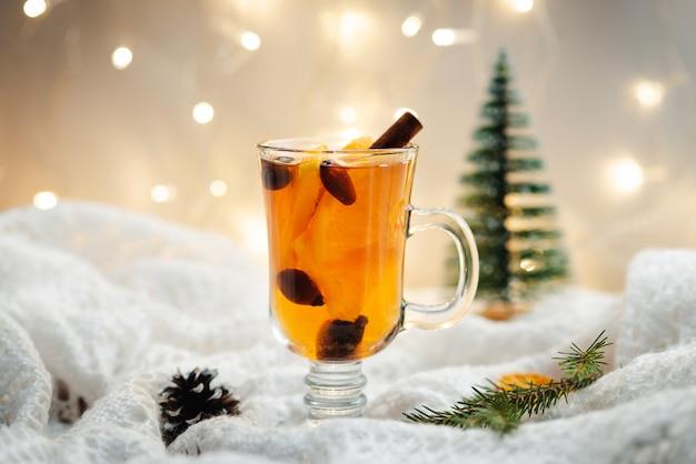 Thé chaud avec de la cannelle, des baies et des oranges sur une couverture de laine blanche