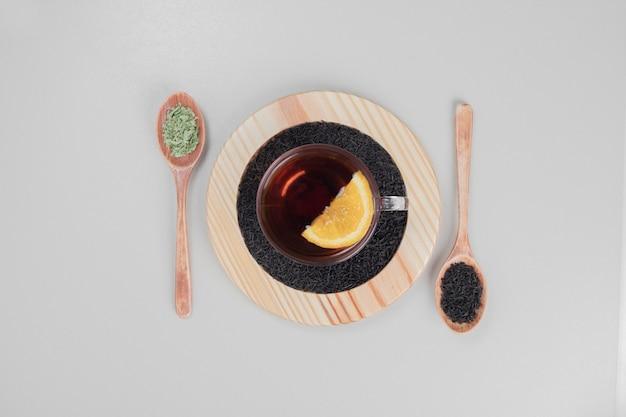 Thé chaud avec des cuillères et du citron sur une plaque en bois