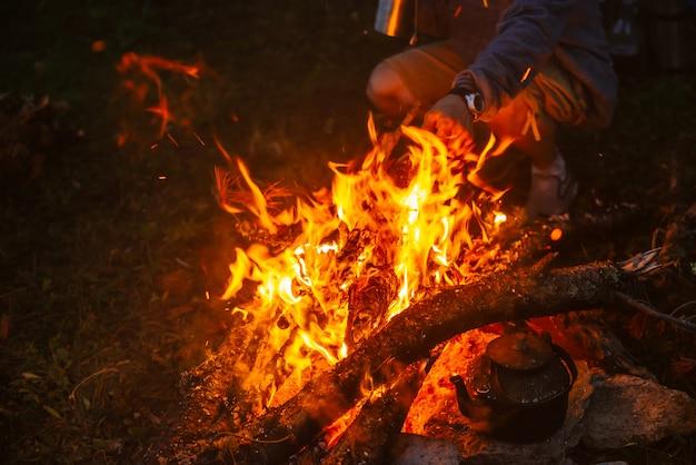 Thé chaud dans une bouilloire sur un feu de joie