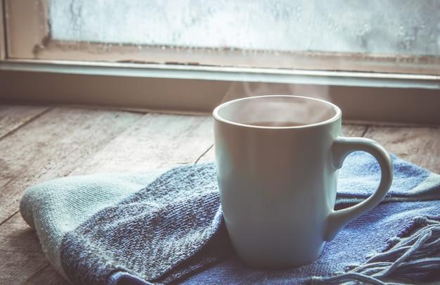Thé chaud dans la casserole près de la fenêtre. mise au point sélective.