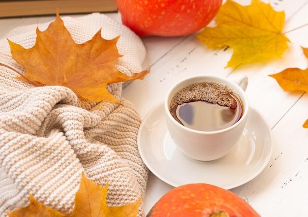 Thé chaud dans une tasse sur un fond d'automne avec des feuilles jaunes