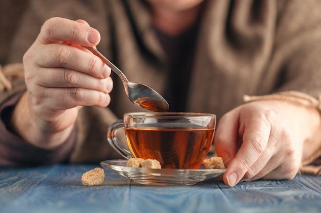 Thé chaud dans une tasse en verre dans les mains des hommes