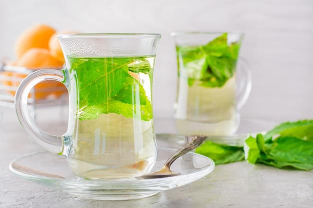 Thé chaud avec des feuilles de menthe dans des verres transparents sur la table