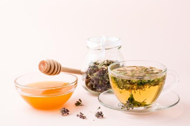 Thé chaud frais avec de l'origan dans une tasse, du miel dans un bol et des herbes sèches dans un bocal. phytothérapie et thérapie alternative