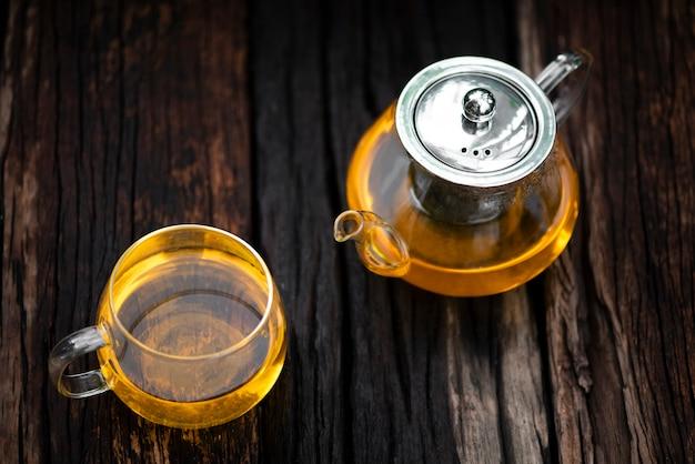 Le thé chaud qui coule de la théière en verre dans la tasse