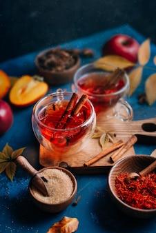 Thé chaud rouge dans des tasses en verre avec des épices