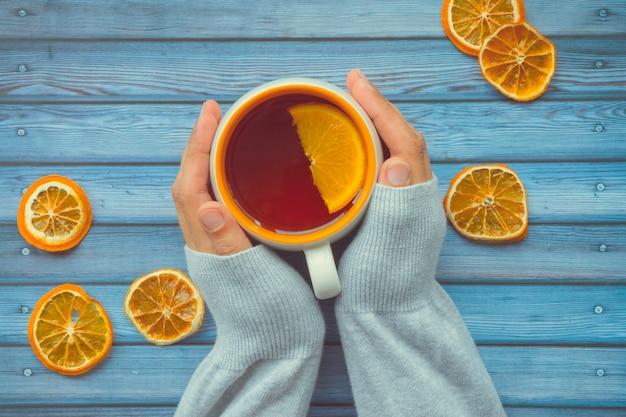 Thé chauffant à l'orange chez les femmes femmes à la main sur une table en bois bleue