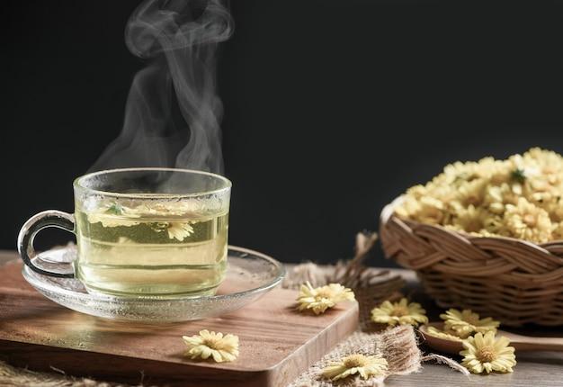 Thé de chrysanthème avec vapeur chaude et fleur de chrysanthème dans le panier sur fond noir