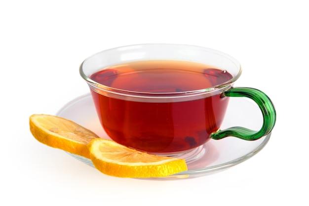Thé avec un citron dans une tasse en verre isolé sur fond blanc. thé noir dans une tasse en verre et sur une soucoupe deux tranches de citron