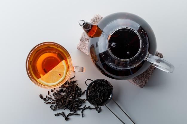 Thé citronné avec théière sur brique, passoire, thé sec dans une tasse sur une surface en dégradé blanc, vue de dessus