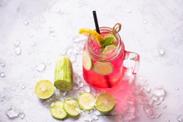 Thé cocktail avec mojito citron vert et concombre, boisson d'été colorée rose rouge juteuse
