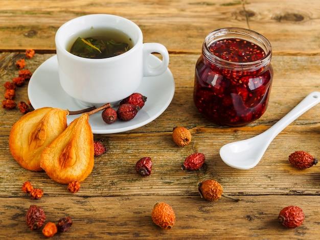 Thé, confiture et fruits secs sur une vieille table en bois.