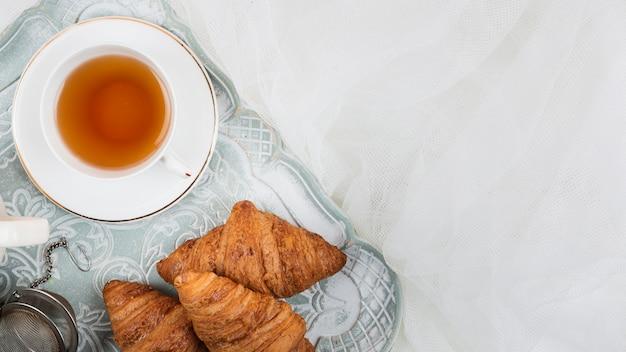 Thé avec des croissants à plat